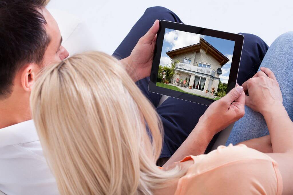 Couple looking at house on tablet